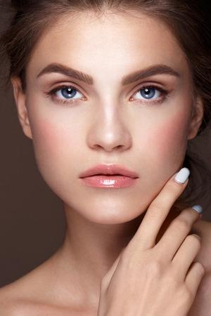 piel: Retrato del encanto del modelo de mujer hermosa con maquillaje fresco todos los d�as y peinado ondulado rom�ntico. Moda resaltador brillante en la piel, los labios atractivos brillantes de maquillaje y cejas oscuras