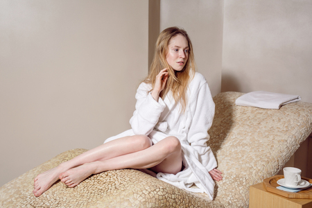 to face to face: young woman wearing a bathrobe sitting on the spa relax room . Biege colour Stock Photo