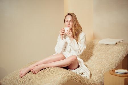 carita feliz: mujer joven que llevaba una bata de ba�o sentada en el balneario relaja el ambiente. de color beige Foto de archivo