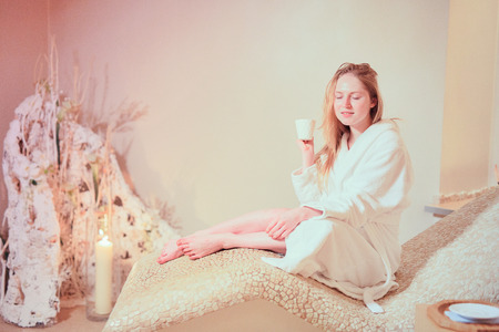 biege: young woman wearing a bathrobe sitting on the spa relax room . Biege colour Stock Photo
