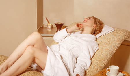 wash face: young woman wearing a bathrobe sitting on the spa relax room . Biege colour Stock Photo