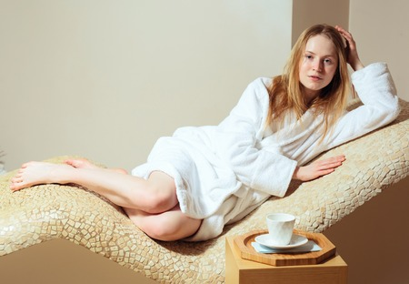 happy healthy woman: young woman wearing a bathrobe sitting on the spa relax room . Biege colour Stock Photo