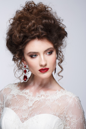dishevel: Beautiful young woman with long brown hair in wedding dress Pretty model poses at studio. Stock Photo