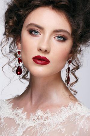 poses de modelos: Hermosa mujer joven con el pelo largo y casta�o en vestido de novia bonita del modelo posa en el estudio.