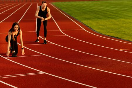 Beautiful sporty woman and young sporty man are ready to run on racetrack.
