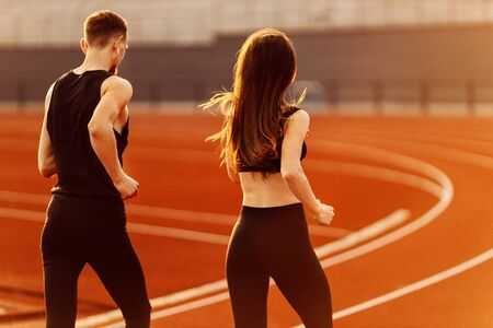 Young man and woman running wearing black sport suits in modern stadium. 写真素材