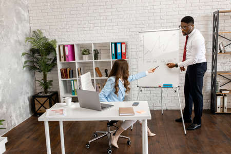 Business professionals. Young confident business peopleanalyze the schedule while spending time in the office