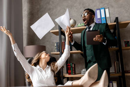 Office concept. Young African man and beautiful young woman work together in the office.