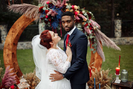 Lovely couple on wedding ceremony, handsome African American man with adorable white woman stand near decorated arch, cuddling, enjoy happy unrepeatable moment, marriage concept. High quality photo
