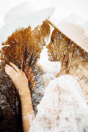 Double exposure with couple and tree branches in autumn park. Sensual atmospheric moment of stylish hipsters looking at each other. Man and woman embracing in hats. Creative unusual photo