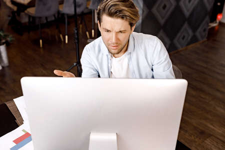 Confused young Caucasian male worker freelancer look at computer screen shocked by gadget breakdown or operational problems. Frustrated man by unexpected error on computer device.