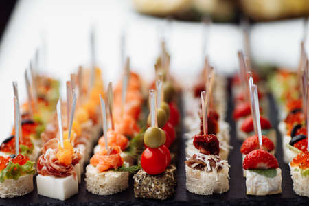 Delicious appetizers and canapes on table at wedding reception in the restaurant. Luxury catering service. Italian delicatessen, prosciutto snacks, cheese and olives. . High quality photo