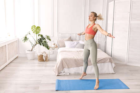 Blonde-hair stylish female is warming up before workout at home, jumping. Athletic young woman doing exercise, smiling, motivate to healthy lifestyle, morning training concept. High quality photo