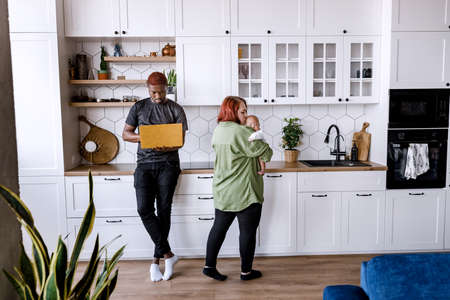 Young interracial family work from home. Red haired young mother embracing lovingly cute child, cooking in the modern kitchen, while Afro American father working online with yellow laptop in hands Stockfoto