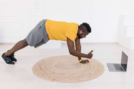Happy young sporty man look at camera showing thumb up, while doing planck exercise,practicing work out using webcam lesson on laptop. Joyful active afro american do routine work out online from home.