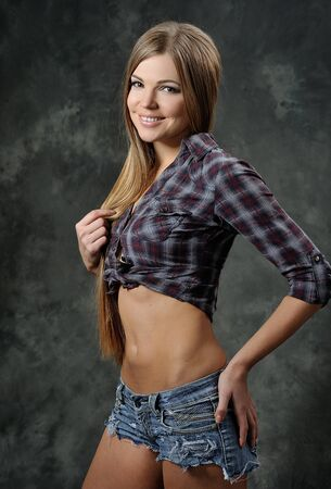 girl in shorts: beautiful girl in shorts and a plaid shirt is smiling