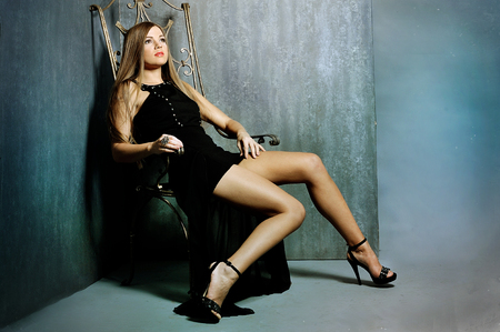 leggy: leggy beauty, in evening dress, sitting on a leather chair in the studio on a gray background.