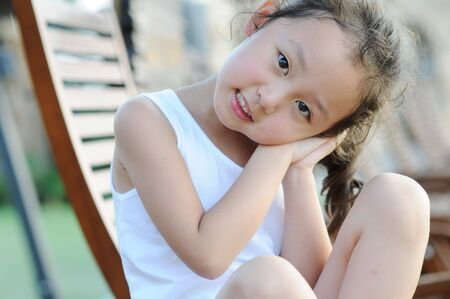 a lovely little girl sitting in a chair photo