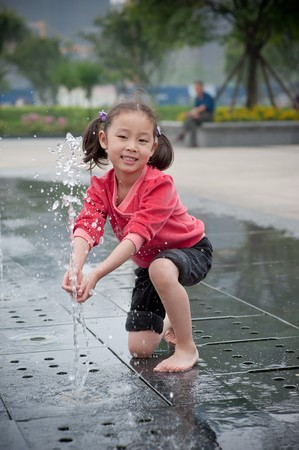 happy asian girl play by Fountain Stock Photo