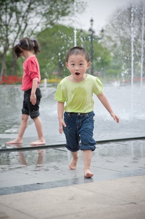 asian boy and girl play by fountain