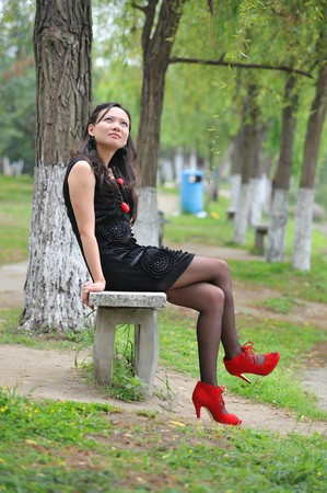 asian woman sit in Chair with  High-heeled shoes photo