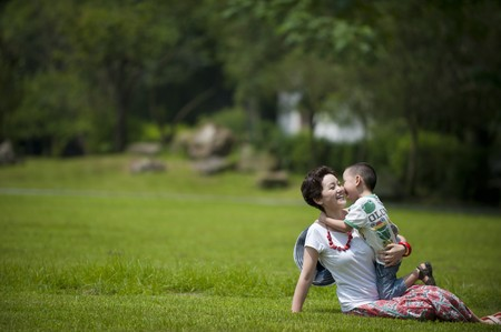 mother and son play in grass