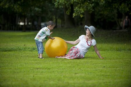 mother and son play ball in grass photo