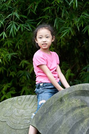 cute little asian girl sit on Stone elephant photo