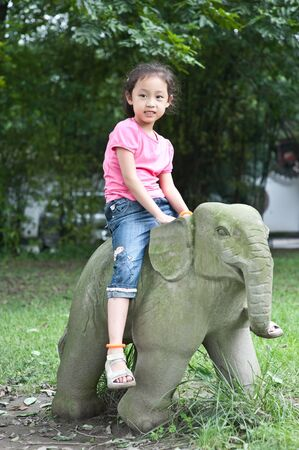 cute little asian girl sit on Stone elephant Stock Photo - 7894192