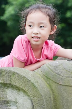 cute little asian girl sit on Stone elephant Stock Photo - 7894170