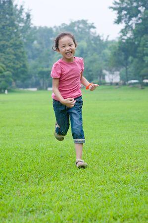 run little asian girl in grass photo