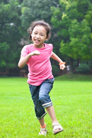 run little asian girl in grass Stock Photo