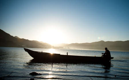 boat fishing in lake,at the sunrise. photo