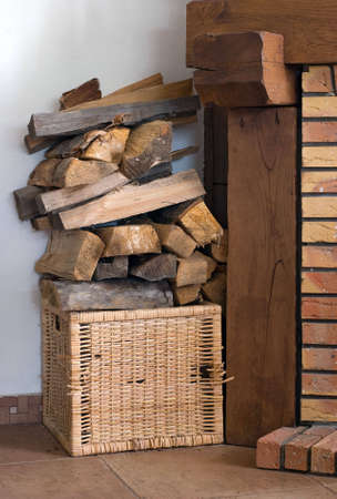 Firewood in a basket near a fireplace Stock Photo