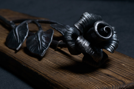 Rose forged from steel on a wooden board. Forging manual. The rose can be hung on the wall. Stock Photo