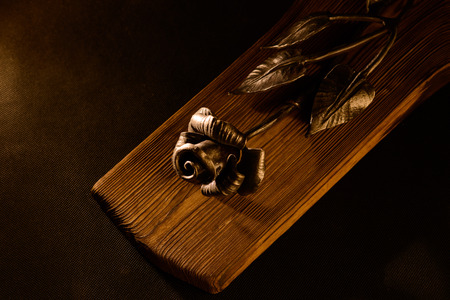hung: Rose forged from steel on a wooden board. Forging manual. The rose can be hung on the wall. Stock Photo
