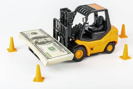 A toy forklift carrying a stack of US dollars Stock Photo