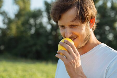 Young farmer sniffing small yellow melon and smiling at organic melon farm. Stock Photo
