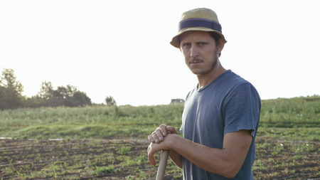 Potrait of caucasian farmer in hat with hoe is resting and looking at camera while removes weeds in corn field at organic farm. Worker lean on the hoe and resting in weeding process.