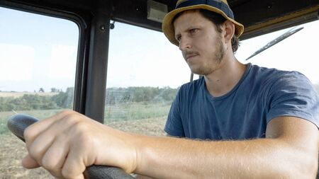 plowing: Portrait of young farmer in hat, sits inside in the tractor cabin, rides on the field. Real plowing process at organic eco farm.