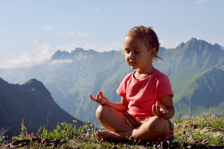 Little cute girl meditating on top of mountain. Portrait of child meditating in lotus pose