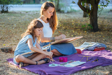oily: Young attractive woman with daughter drawing by watercolor paints at the park. Stock Photo