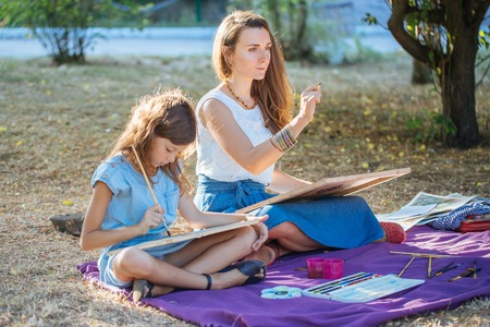 Young attractive woman with daughter drawing by watercolor paints at the park. Stock Photo