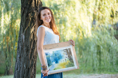 Portrait of charming female artist with picture and brush at the park in sunny summer day. Woman looking at camera and smiling.