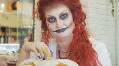 Portrait of redhead woman with halloween makeup in nurse stile with pumpkin.