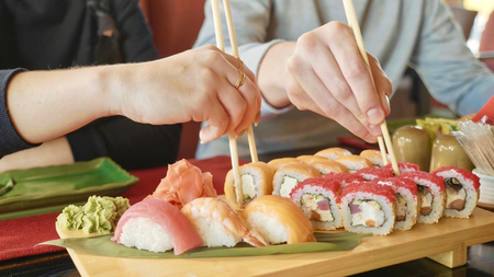 Young couple with chopsticks takes sushi from a plate in a japanese restaurant. Stock Photo