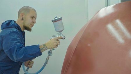 Auto painter spraying red paint on car hood in special booth