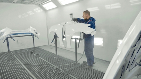 Auto painter spraying white paint on car spare fender in special booth