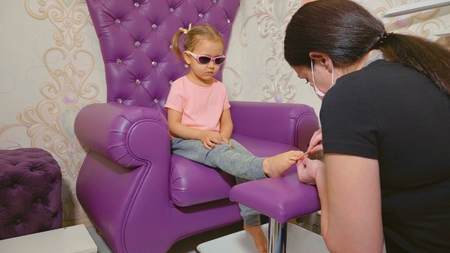Cute baby girl at pedicure procedure in beauty spa salon. Stock Photo