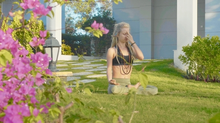 Pranayama yoga breath exercise by a young woman in the backyard of her house. Stock Photo